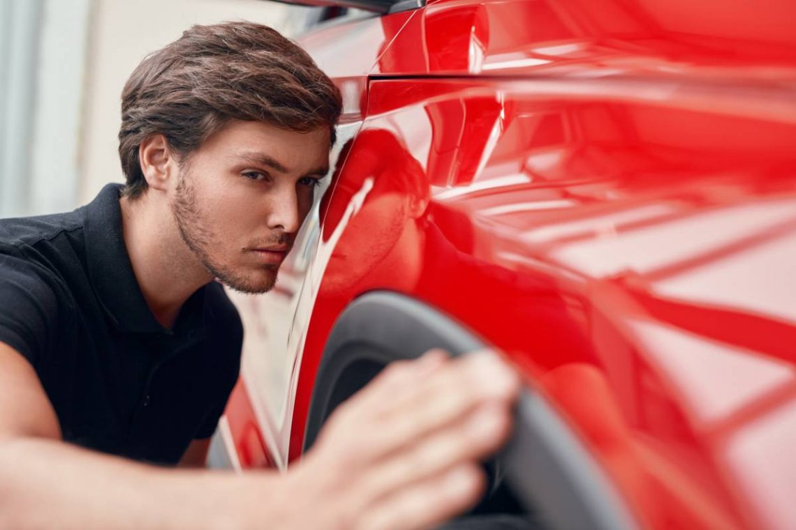 Un client en train de vérifier une voiture d'occasion qu'il souhaite acheter